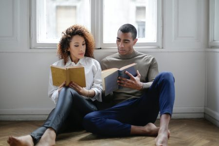 man-and-woman-sitting-on-the-floor-reading-book-3967013